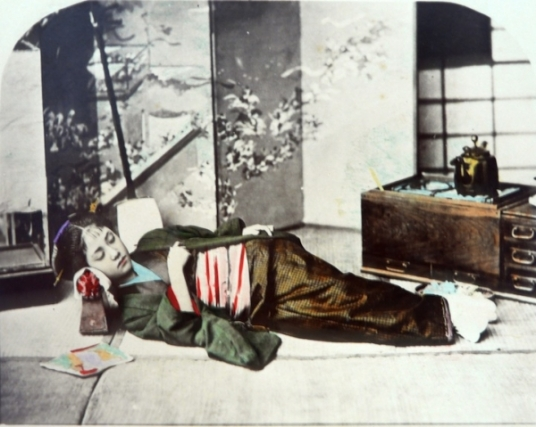 Geisha sleeping on takamakura. 1888-1908, hand-tinted. by Adolfo Farsari